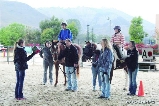 サンワンカピストラーノにあるシェイ・センターで行われている乗馬療法で、インストラクター、ハサウェイさん(左端)の指導を受けるニコールちゃんと自閉症のメイソン・バンくん(13)