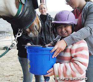 セッション終了後、お世話になった馬にニンジンをあげるニコールちゃん