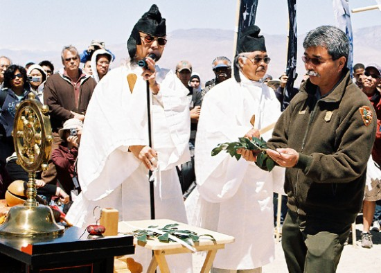 Manzanar Superintendent Les Inafuku makes an offering at the cemetery monument during the Manzanar Pilgrimage in 2009. (Photo by Martha Nakagawa)