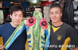 Fujimaki, left, and Miya show one of their amphibian-style costumes. They also apply their own makeup, a task that takes up to two hours. (MIKEY HIRANO CULROSS/Rafu Shimpo)