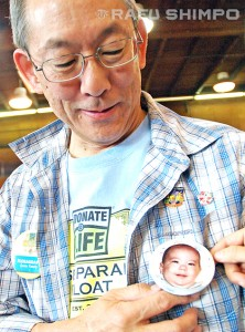 Bruce Endo displays a button bearing a photo of his son, Andrew, who was also pictured on the float. The baby died as a result of SIDS in 1981.