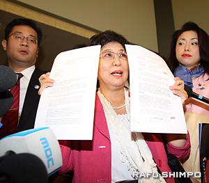 日韓のメディアに囲まれ、グレンデール市に提出した抗議文と慰安婦に関する米公文書のコピーを披露する松浦芳子団長(中央)