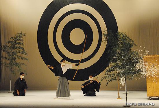 仲村哲也さんのハーモニカ演奏を伴奏に行われた初矢の清めの儀式で弓を引く小阪博一さん