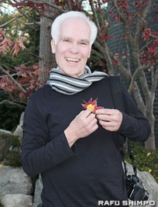 Gil Garcetti wearing his trademark muffler and holding maple and ginkgo leaves from his garden. (JUNKO YOSHIDA/Rafu Shimpo)