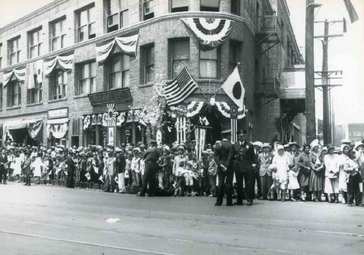 Throngs of people line up beneath Japanese and American flags draped in front of Los Angeles Hompa Hongwanji Buddhist Temple at First Street and Central Avenue for a parade honoring visiting royalty, Prince Takamatsu, the younger brother of Emperor Hirohito, in 1931. Ironically, Prince Takamatsu was wary of both Japanese colonial expansion and war with the United States. (Photo courtesy of Alan Miyatake/Toyo Miyatake Studios)