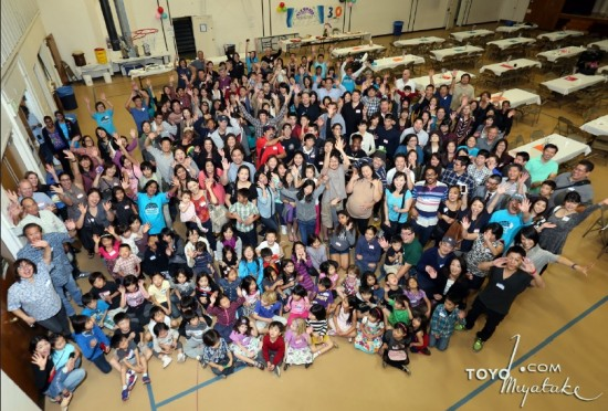 Current and former attendees of the Nishi Hongwanji Child Development Center gather for a group photo at a reunion held in December. (Toyo Miyatake Studio)
