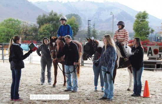 On horseback, Nicole Matsushita (right) and Mason Vann (left) listen to their certified instructor, Ashley Hathaway, at a therapeutic riding session Nicole at Shea Center in San Juan Capistrano.