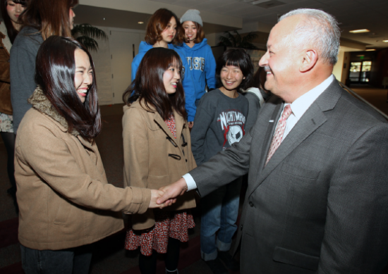 Cal State San Bernardino President Tomás Morales shaking hands with an exchange student from Yasuda Women's University in Hiroshima.