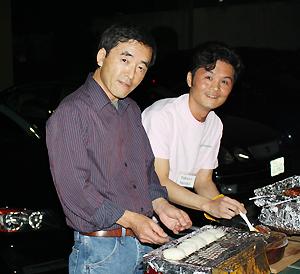 岐阜名物の五瓶餅を焼く樋田研二さんと鈴木琢也さん