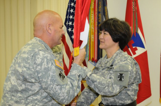 Army Reserve Brig. Gen. Miyako Schanely, deputy commander of 412th Theater Engineer Command in Vicksburg, Miss., returns her general officer flag to Command Sgt. Maj. Ronald Flubacher, senior enlisted advisor for the 412th TEC, for safekeeping during her promotion ceremony.