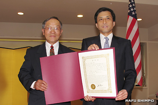 Tak Nishi (left) receives a commendation from Consul General Jun Niimi.