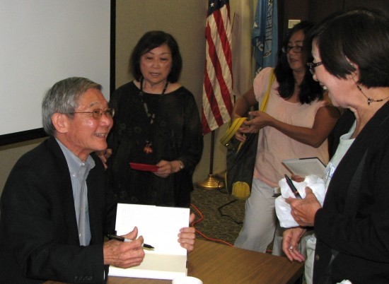 Franklin Odo signs copies of his book during an appearance in Torrance last year. (J.K. YAMAMOTO/Rafu Shimpo)