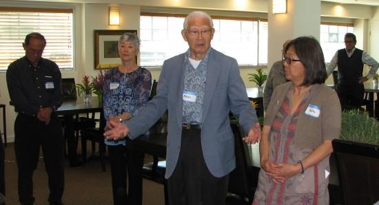 Rev. Paul Nagano (center) gives an invocation at the beginning of the Shinnenkai. At right is Kathy Masaoka of NCRR. (J.K. YAMAMOTO/Rafu Shimpo)