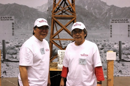 Director/co-producer Cory Shiozaki and writer/co-producer Richard imamura in front of a facsimile Manzanar guard tower at the 2011 Fred Hall Show.