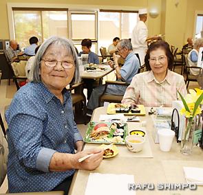 好物のすしを食べ、大喜びの敦子ハムトンさん(左)と松岡俊子さん