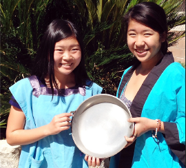Volunteers Lani Masumoto (left) and Lorie show off an individual sukiyaki pan.
