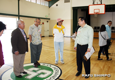 Kenji Watanabe explains improvements made to the gymnasium at SFVJACC, including painting the logo at center court, during a tour of the center's facilities.