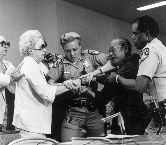 During the Los Angeles hearings of the Commission on Wartime Relocation and Internment of Civilians in August 1981, Lillian Baker tries to grab Nisei veteran Jim Kawaminami's testimony from his hands. Baker, a controversial conservative author and lecturer from Gardena, denied that Japanese Americans were incarcerated during World War II.