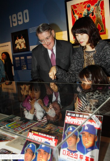 Former Dodgers owner Peter O'Malley and Ri-hye Park, wife of pitcher Chan Ho Park, examine a display of memorabilia. (MARIO G. REYES/Rafu Shimpo)