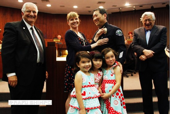 Torrance Police Chief Mark Matsuda receives his new badge from his wife Kristin at the Torrance City Council meeting on Tuesday. They are joined by their daughters Sophie, Mathilde and Candice; Torrance Mayor Frank Scotto (left) and Leroy Jackson, city manager. (MARIO G. REYES/Rafu Shimpo)