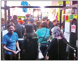 QPop co-owner Chris Mitchell, left, welcomes some of the throngs of visitors on Saturday night.