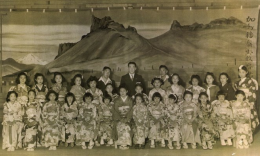 Sahomi Tachibana and her students at Tule Lake. Stage backdrop of Castle Rock and Mt. Shasta painted by Enjiro Kodani.
