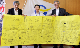 Sensuke Shishido (right) meets with Date City Board of Education members. They are holding a banner sent to Fukushima by Dwyer Middle School students in Huntington Beach.