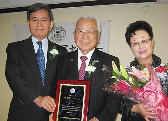 半田新会長(左端)から感謝の盾と花束を贈られた宮崎夫妻
