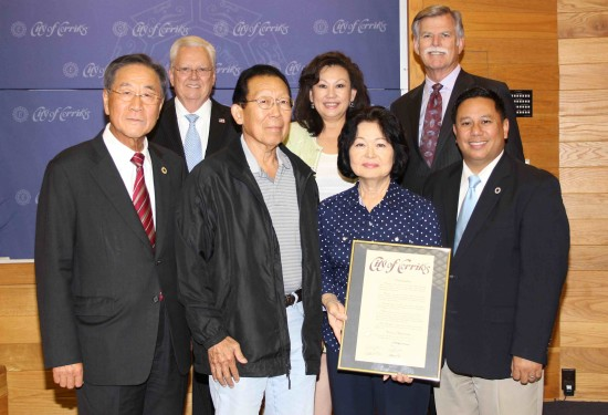Front row, from right: Cerritos Mayor Mark Pulido, honoree Kimie Matsumoto and her husband Fred, City Councilmember Joseph Cho. Back row, from right: Councilmember Bruce Barrows, Mayor Pro Tem Carol Chen, Councilmember George Ray.