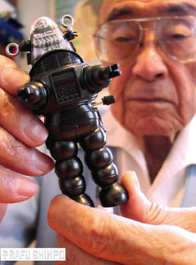 Robert Kinoshita displays a miniature model of his creation, Robby the Robot, at his Torrance home in 2004. (Photo by MARIO G. REYES/Rafu Shimpo)