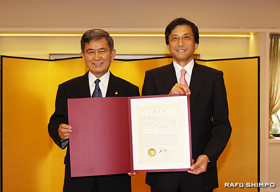 新美潤総領事(右)から表彰状を授与される半田さん