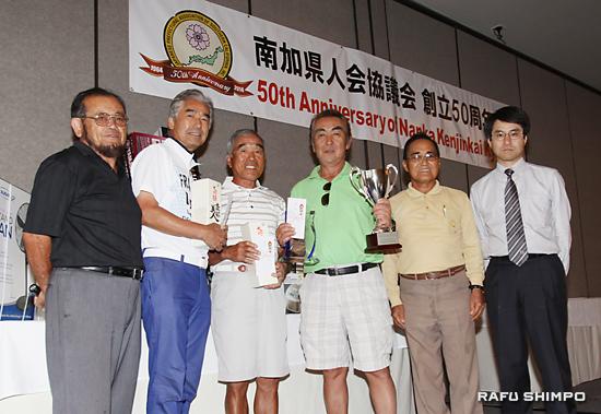 130人が参加した大会の表彰式。左から西元大会委員長、2位平野さん、3位福田さん、優勝者山県さん、当銘会長、新村領事