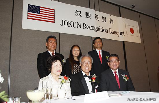 メインテーブルで、叙勲者と主要団体代表の記念撮影。前列左から中村夫妻、後列左が青木会頭、右は新美総領事