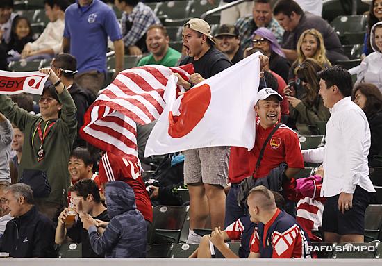星条旗に対抗して、日章旗を広げて応援するゴジラ・ラグビーチームのメンバー