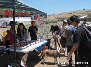 スイカを配るブースでボランティアするオレンジコースト・オプティミストクラブのメンバー