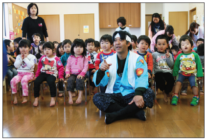 Momotaro (Grateful Crane's Kurt Kuniyoshi) poses with preschoolers in Ishinomaki.