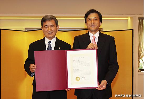 Toshio Handa (left) receives the commendation from Consul General Jun Niimi. (JUN NAGATA/Rafu Shimpo)