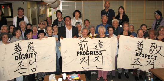 "L.A. City Councilmember Jose Huizar (center) joins seniors and Little Tokyo Service Center staff members in holding banners reading ""Dignity,"" ""Respect"" and ""Progress"" in English, Japanese and Korean."