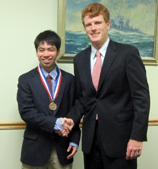 Rep. Joseph Kennedy congratulates Jordan Bradley Inouye Helfand at his district office on May 11.