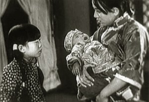 "Wang Renmei (holding baby) in ""The Song of the Fishermen."""