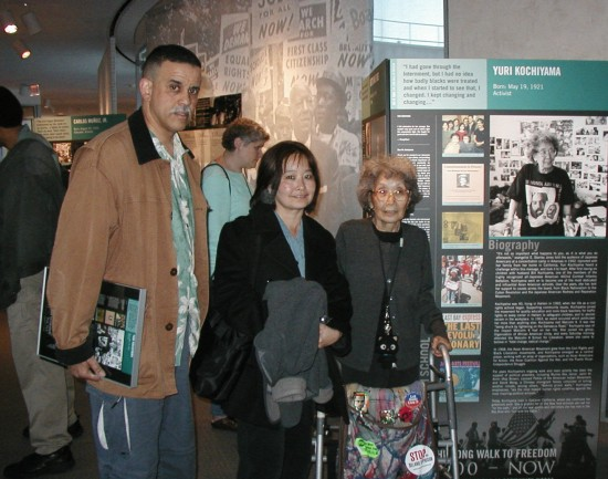"""Yuri Kochiyama, accompanied by daughter Audee Kochiyama Holman and son-in-law Herb Holman, at the opening of """"Long Walk to Freedom"""" at the San Francisco Public Library in 2003. Yuri was one of 12 civil rights leaders recognized in the exhibit. (Hokubei Mainichi)"""