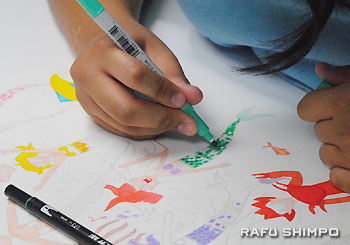Hikaru carefully colors mermaids with vibrant color markers.