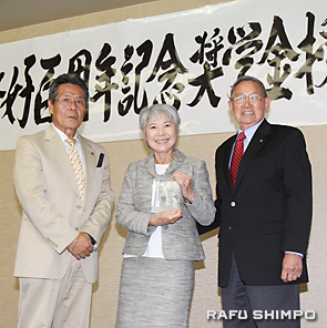 青木会頭(左)から功労表彰の楯を授与されるリーさん夫妻