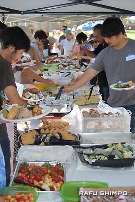 長テーブルに並んだ会員の豪勢な手料理