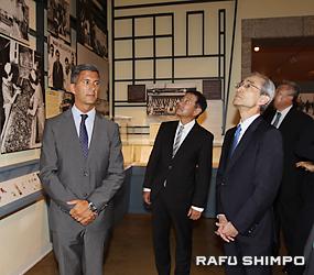 日系人の古い写真を熱心に見る日系人の平野頭取(右)