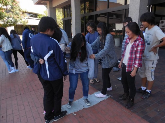 Members of Rising Stars 11 participate in an icebreaker exercise on the JACCC Plaza as part of the teamwork session. From left: Yuki Mano, Sharyse Watanabe, Dani Yang, and Erika Higa on the mat with (from left) Ariel Imamoto, Bryron Brown, Hiro Ozaki, and Lindsay Taguchi looking on.