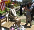 A cameraman shoots the comfort women monument in Glendale after its unveiling last year. (Rafu Shimpo photo)