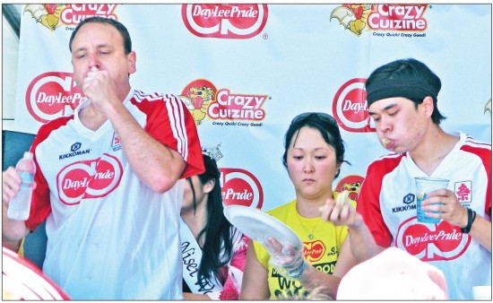 Joey Chestnut, left, and Matt Stonie, right, chomp down fried dumplings Sunday, during the 2014 Day-Lee Foods World Gyoza Eating Championship, held near the Go For Broke monument in Little Tokyo.