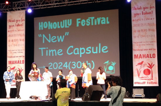 : Students place messages into a time capsule at the Honolulu Festival in Hawaii. The time capsule will be opened in 2024. (GWEN MURANAKA/Rafu Shimpo)