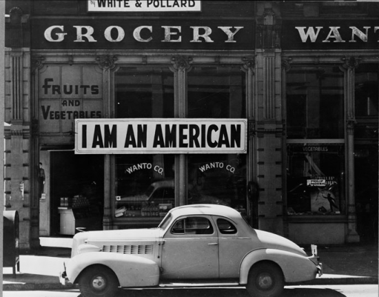 "Oakland, March 1942. A large sign reading ""I am an American"" placed in the window of a store at 13th and Franklin Streets on Dec. 8, the day after Pearl Harbor. The owner, a University of California graduate, was among the Japanese Americans removed from the West Coast. (Dorothea Lange for U.S. War Relocation Authority)"